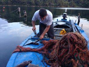 Fischer auf Boot nimmt Fische aus